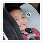 A smiling five-year-old in a car seat.